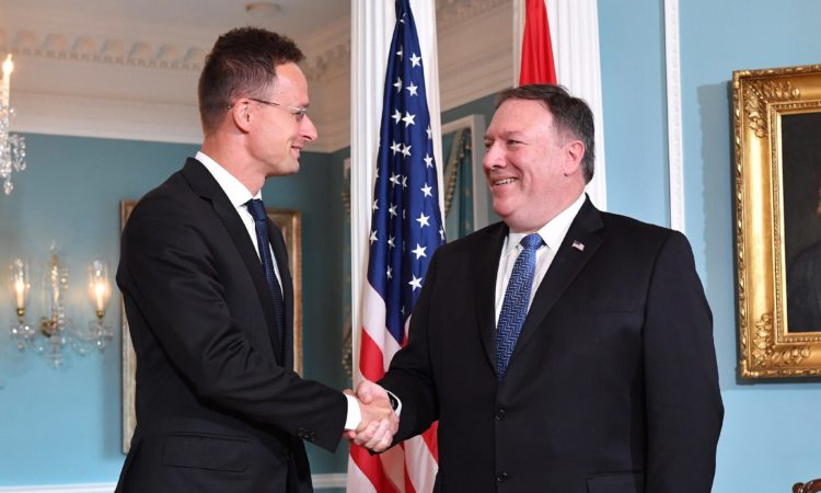 two white men in suit and tie shaking hands and smiling at each other