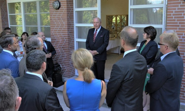 a white man in suit talking in front of a semicircle of audience in a doorway