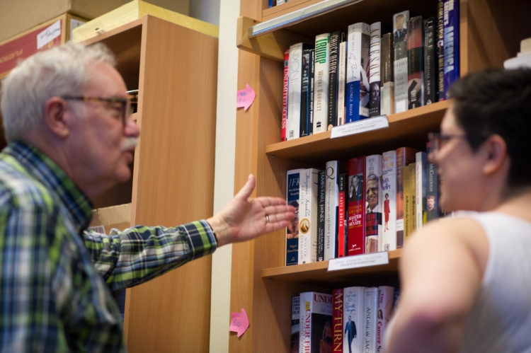 older man and young woman talking in front a bookcase full of books
