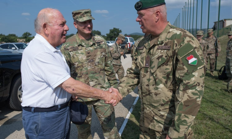 a soldier in uniform shakes hands with civilian while other soldier is looking on