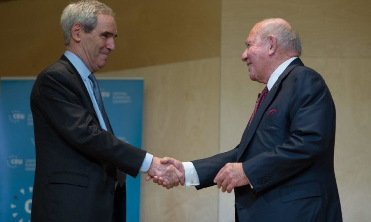two grey haired men in suit shaking hands and smiling