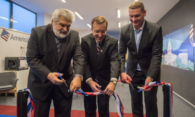 three men cut a ribbon