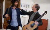 two men smiling at each other with guitars in hand