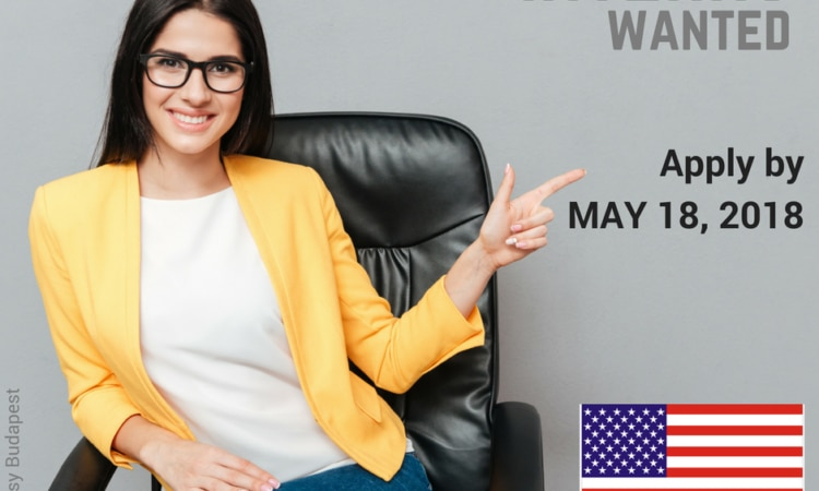 young woman wearing glasses, sitting, pointing at 'Apply now' sign
