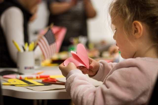 little girl looking at heart shaped pink paper sitting at table